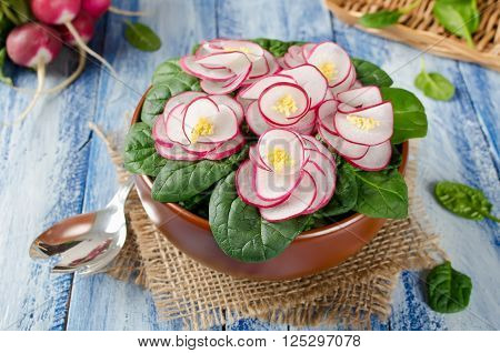 Vegetable salad Violet on blue wooden table. Salad decorated with flowers from radish and spinach leaves