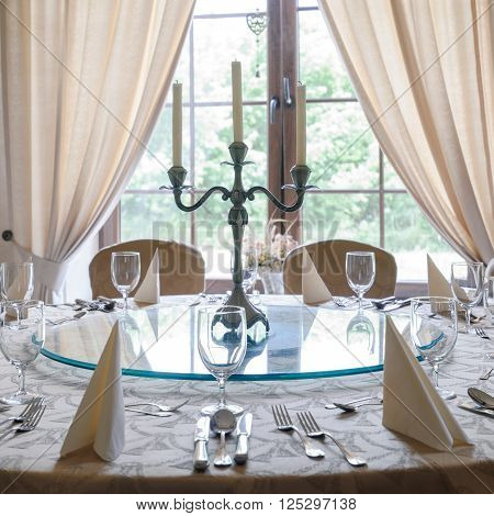 Round table with glasses cutlery and candlestick in elegant luxurious restaurant