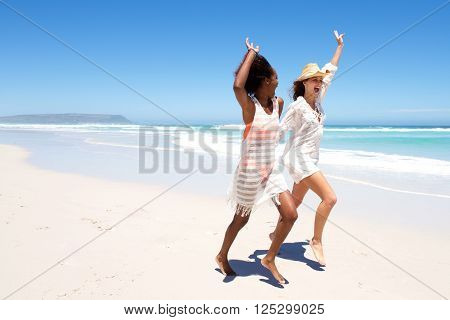 Young Female Friends Laughing And Playing On The Beach