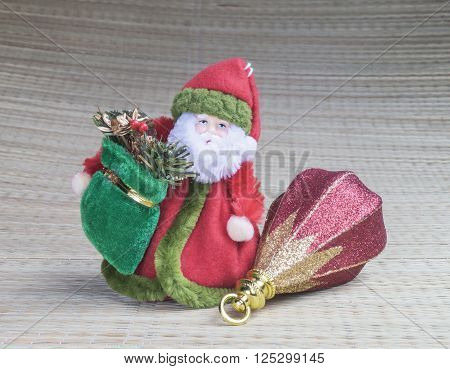 Grandparent Frost in red caftan with toy on gray background