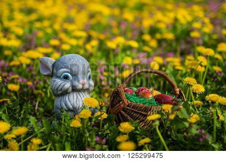 Easter eggs in basket with rabbit on green grass meadow with flowers