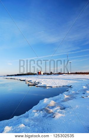 Frozen sea landscape with ice and snow. Meteorological station in distance.