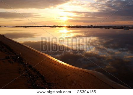 Sunset at the sea shore. Beautiful sky reflecting in still water. ** Note: Visible grain at 100%, best at smaller sizes