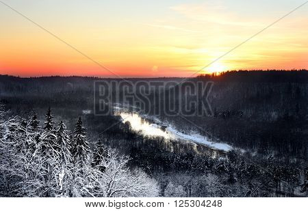 Winter sunset in snowcovered Gauja river valley. Sigulda, Latvia.
