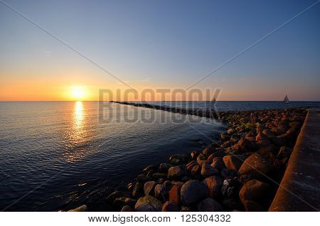 Sunset at the sea shore. Stone breakwater road leading to the setting sun.