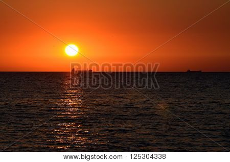 Colourful orange sunset at the sea. Clear red sky.