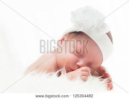 Newborn baby with headband sleeping on white fur. White background.