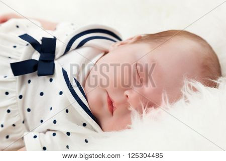 Newborn baby sleeping on white fur blanket. Wearing sailor dress. Maritime