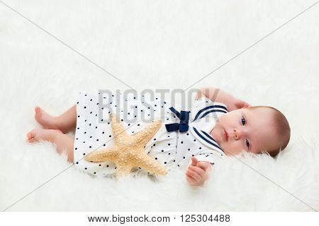 Newborn baby lying on white fur blanket. Maritime composition with starfish and sailor dress.