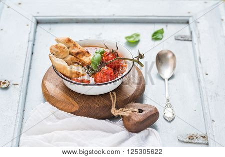 Italian tomato, garlic and basil soup Pappa al Pomodoro in metal bowl with bread on rustic wooden board over light blue background