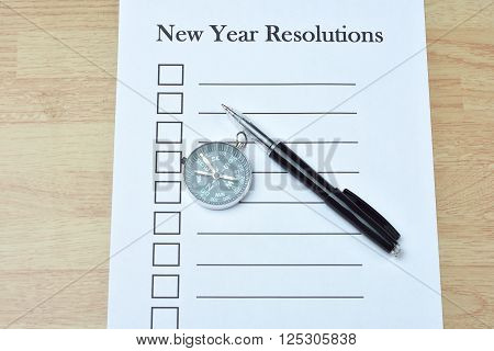 Concept : pen and compass on note book with checklist box on wood background New Year Resolutions phrase