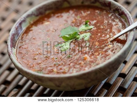 Closeup view of a bowl of freshly made gazpacho soup with cilantro garnish