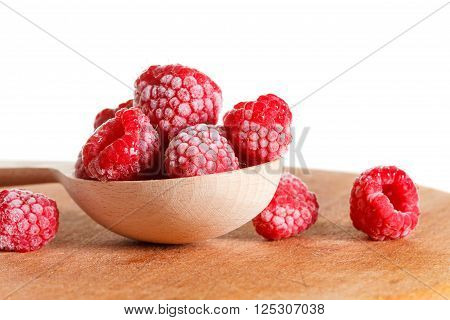 Frozen raspberries on the cutting board in a wooden spoon closeup with snow and ice. Isolated on white background