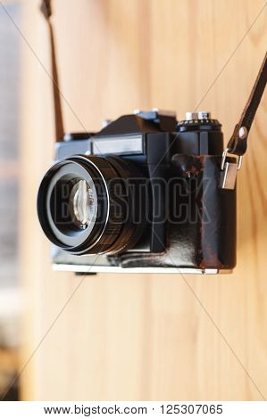 Old camera in a leather case hanging on wooden wall closeup selective focus vertical ** Note: Shallow depth of field
