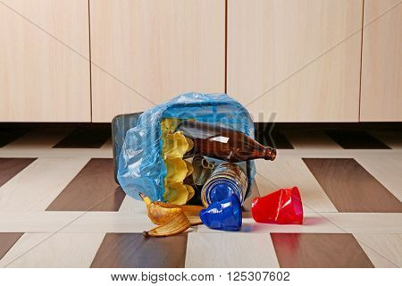 Full inverted garbage basket on kitchen floor