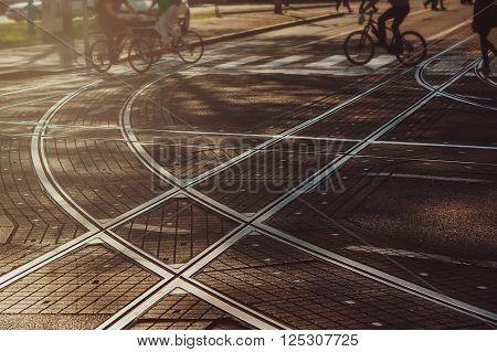 Tram lines intersection on the paved street in Zagreb, Croatia, intentionally blurred background with people going from work, bicyclists, commuters