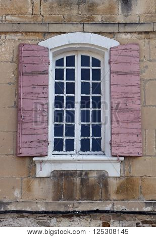 Old window exterior with open shades on decayed facade