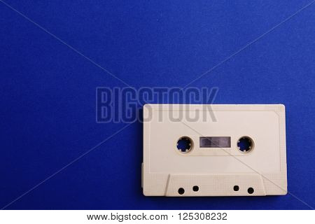 Old audio cassette on blue background