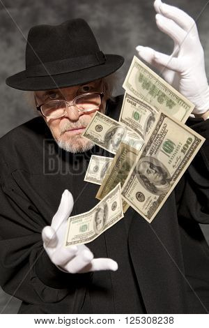 Magician show with dollars banknote. On grey background