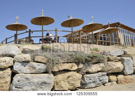 MARBELLA, SPAIN -APRIL 9, 2016: Couple kissing in the terrace of a beach bar in Marbella a city in southern Spain belonging to the province of Malaga Andalusia Spain