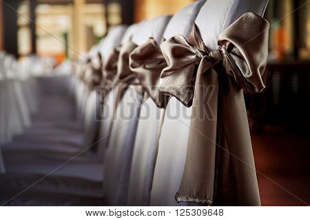 line of  garnished chairs with fattys on wedding day