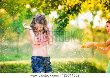 Boy splashing girl with water gun, fun in garden, sunny summer day, back yard