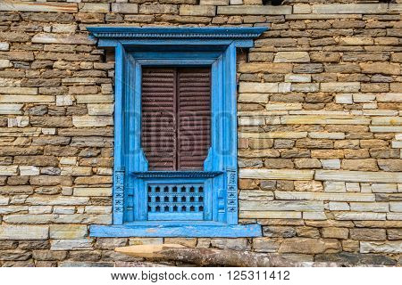 A traditional Nepalese window, blue frame and brown shutters