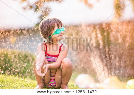 Cute girl crouching in the garden under the water splashing from sprinkler, sunny summer back yard