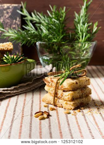 Home made stacked butter cookies with rosemary, pignoli and pistachio nuts on table cloth with rosemary sprigs and a hot beverage in the background, vertical shot