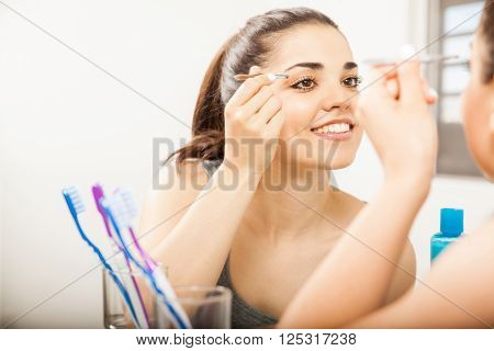 Reflection Of A Woman Plucking Her Eyebrows