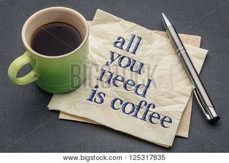 All you need is coffee - handwriting on a napkin with cup of coffee against gray slate stone background