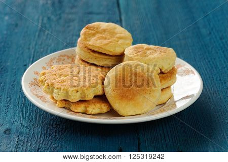 Plate of tasty imperfect homemade cookies on deep blue background closeup