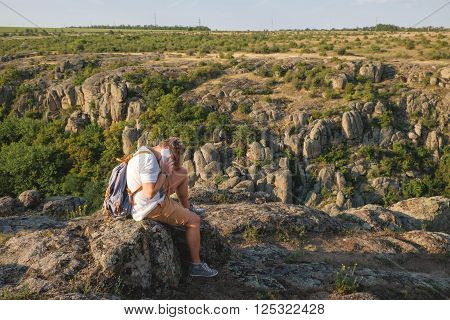 Young Man With A Beard Sitting On Canyon Cliff