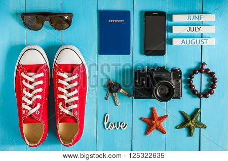 Summer outfit of traveler, student, teenager, girl, young woman or guy. Overhead of essentials for modern Young person. Different objects on blue wooden background.