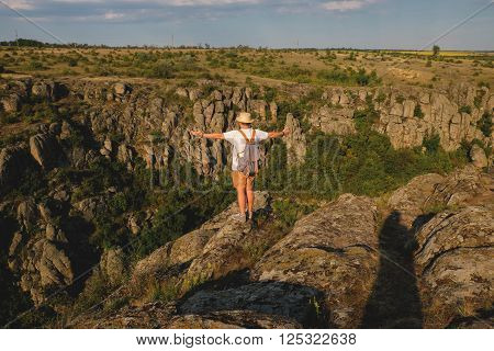 Stylish young man with beard standing on the precipice of the canyon. View from the back