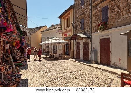 MOSTAR, BOSNIA AND HERZEGOVINA-JULY 20 2014: People walking through the Old Town with many shops and cafes on July 20, 2014 in Mostar, Bosnia and Herzegovina. Mostar is situated on the Neretva River.