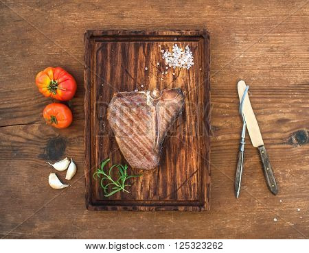 Cooked meat t-bone steak on serving board with garlic cloves, tomatoes, rosemary and spices over rustic wooden background, top view