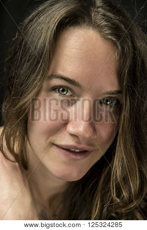 Close up portrait of woman looking straight, isolated on black background