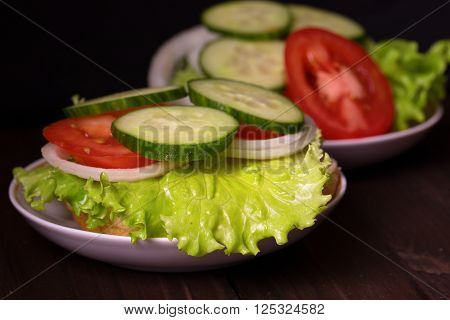 Bread with salad and other vegetables lies on a saucer. On a half of a roll the lettuce leaf onions rings a tomato piece sausage lies. Close up small depth of sharpness