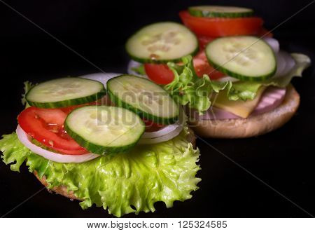 Sandwich with salad and other vegetables on a black background. On a half of a roll the lettuce leaf onions rings a tomato piece sausage lies. Close up small depth of sharpness
