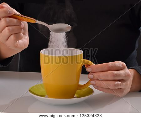 Woman pouring sugar on coffee cup.