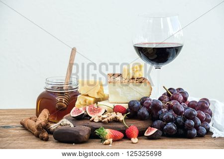Glass of red wine, cheese board, grapes, fig, strawberries, honey and bread sticks  on rustic wooden table, white background, selective focus, closeup