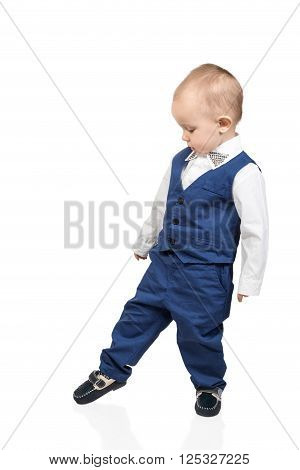 Little boy in formal suit blue and shoes make a cautious step isolated on white background