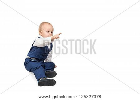 Little boy in a blue suit sitting on the floor and the side indicates his forefinger isolated on white background