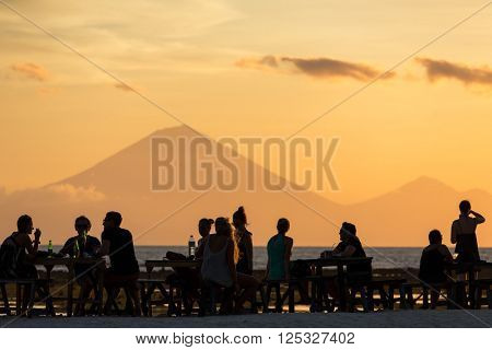 Tourists in the restaurant on Gili Travangan island enjoying evening sunset view on Gunung Batur volcano on Bali, Indonesia.