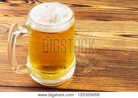 Mug of cold beer on wooden table close-up view