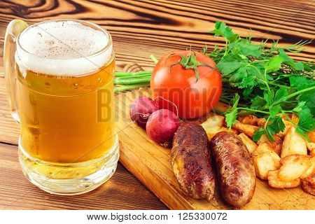 Grilled meat sausages with fried potatoes fresh produce and mug of beer on wooden board.