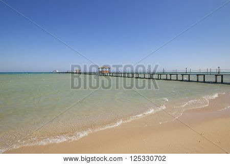 Red Sea beach with clean turquoise water and a pier stretching into the distance