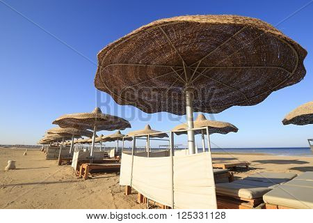 Sea beach with straw umbrellas and sunbeds