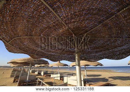 Bottom of straw beach umbrella at the sea beach